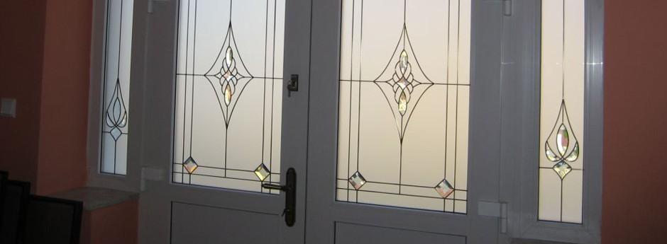 Szklane - witrażowe wykończenie drzwi wejściowych do domu